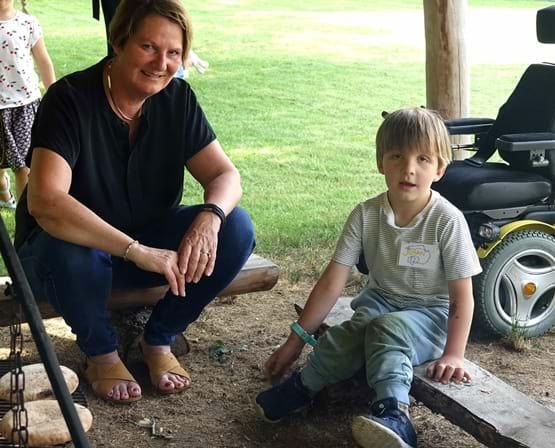 Centerbørnehavens leder sidder ved bålplads sammen med dreng med cerebral parese